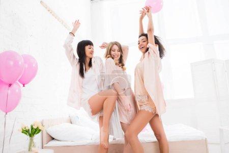 Photo pour Heureux émotionnel multiculturel filles dansant avec des ballons roses dans la chambre - image libre de droit