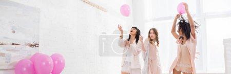 Foto de Foto panorámica de chicas multiculturales alegres que se divierten con globos rosas en el partido bachelorette. - Imagen libre de derechos