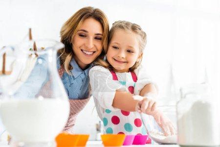Photo pour Concentration sélective de belle mère et fille préparant des cupcakes avec des ingrédients, y compris le lait et la farine dans la cuisine - image libre de droit