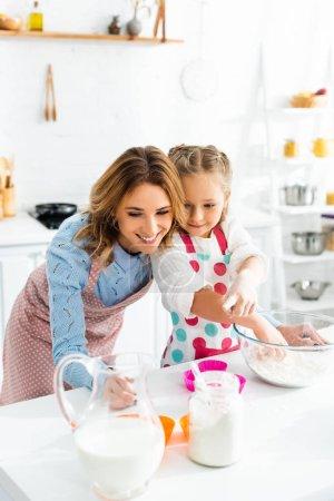Photo pour Belle mère et jolie fille préparant des cupcakes avec des ingrédients, y compris le lait, la farine dans la cuisine - image libre de droit