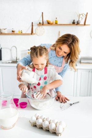 schöne Mutter und niedliche Tochter sieben Mehl in eine Schüssel auf dem Tisch in der Nähe von Teigformen, Eiern, Milchkrug und Luftballonbesen