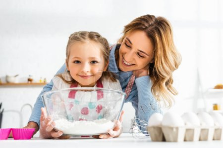 enfoque selectivo de mamá feliz y linda hija sosteniendo tazón con harina en la cocina