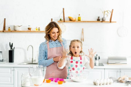 Photo for Cute daughter with open mouth holding up hands standing with mom at table - Royalty Free Image