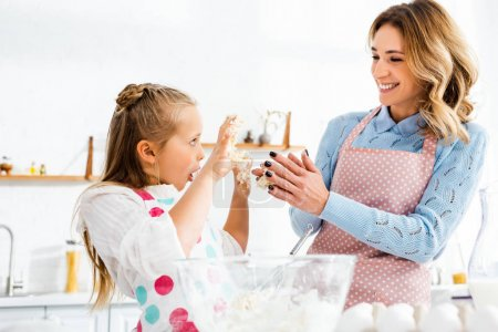 Photo for Selective focus of smiling mom and daughter with open mouth holding up hands having fun during kneading dough - Royalty Free Image