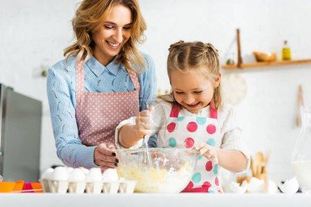 Photo pour Belle mère attrayante et fille mignonne cupcakes de cuisine heureux et positifs ensemble à la maison - image libre de droit