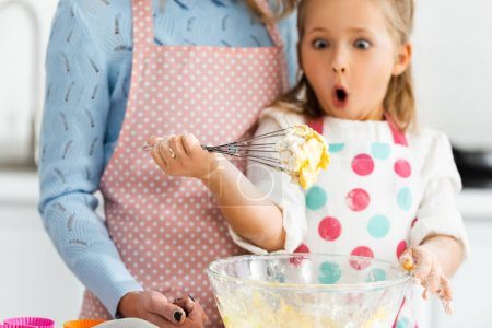 Photo for Selective focus of shocked and excited child looking at balloon whisk in dough above bowl - Royalty Free Image