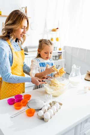 Photo for Mother and daughter in aprons mixing dough in kitchen - Royalty Free Image