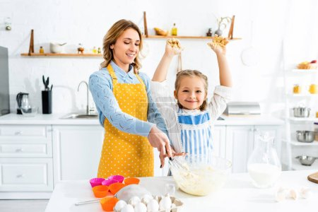 Photo pour Une mère et sa fille souriantes dans des tabliers mélanger la pâte à la cuisine - image libre de droit