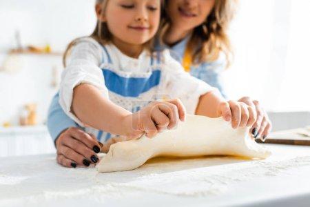 abgeschnittene Ansicht von Mutter und lächelnder Tochter beim Kochen von Gebäck