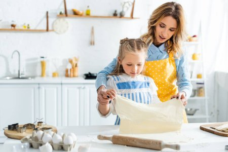 Photo for Attractive mother and cute daughter holding dough during cooking in kitchen - Royalty Free Image