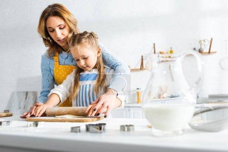 Photo pour Mère attrayante et fille mignonne rouler la pâte sur la planche à découper - image libre de droit