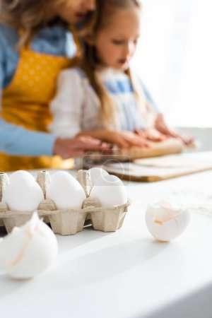 Photo for Selective focus of eggs in carton box and egg shells on table - Royalty Free Image