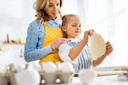 selective focus of mother looking at daughter with dough