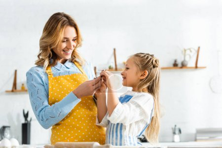 Photo for Smiling mother and cute daughter holding dough mold in kitchen - Royalty Free Image