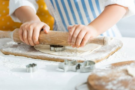 Photo for Cropped view of kid rolling dough with rolling pin - Royalty Free Image