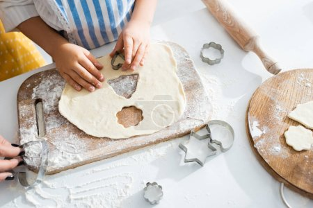 Photo for Cropped view of daughter cooking cookies with dough molds - Royalty Free Image