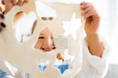 Selektiver Fokus von Mutter und lächelnder Tochter, die Teig für Plätzchen halten