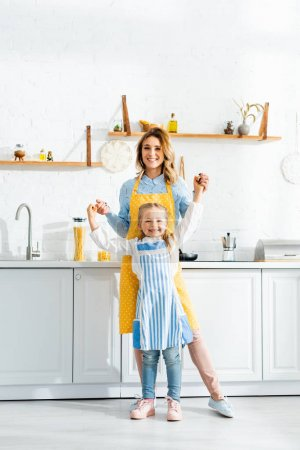 Photo for Smiling mother holding hands with daughter and looking at camera in kitchen - Royalty Free Image