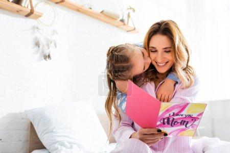 Photo pour Fille embrasser mère souriante avec carte dans la fête des mères - image libre de droit