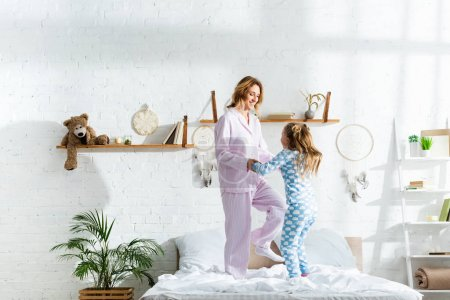 Photo for Smiling mother and daughter holding hands and jumping on bed - Royalty Free Image