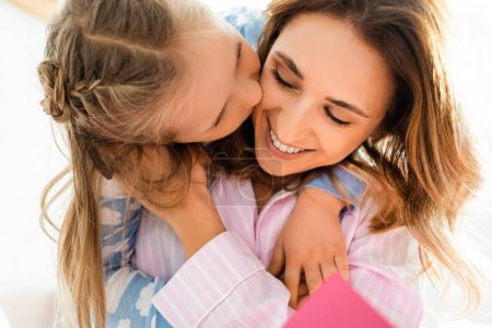 Photo for Cute daughter kissing smiling and attractive mother in bedroom - Royalty Free Image