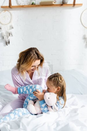 Photo for Smiling mother and daughter in pajamas playing on bed - Royalty Free Image