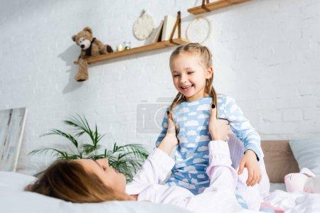 Photo pour Mère tenant et jouant avec fille souriante sur le lit - image libre de droit