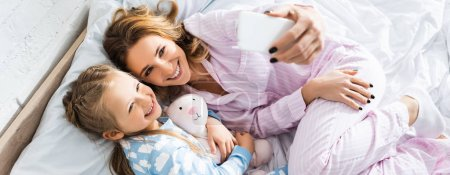 panoramic shot of smiling mother taking selfie with cute daughter