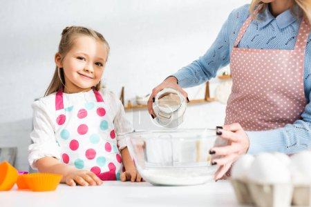 Photo pour Vue recadrée de mère ajoutant de la farine au bol et fille souriante regardant la caméra - image libre de droit