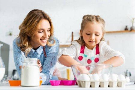 sonriente madre mirando hija cocinar masa para pastelería