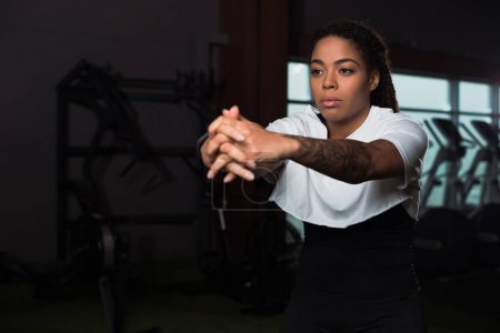 Selective focus of african american attractive woman clenching hands and training in gym