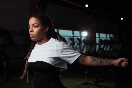 Photo pour Femme afro-américaine s'étirant avant l'entraînement en salle de gym - image libre de droit