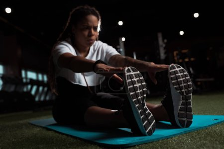 Photo for Selective focus of african american woman sitting and stretching on fitness mat - Royalty Free Image
