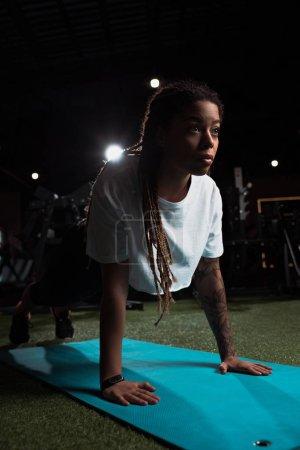 Mujer afroamericana de pie en tablón en la alfombra de fitness en el gimnasio