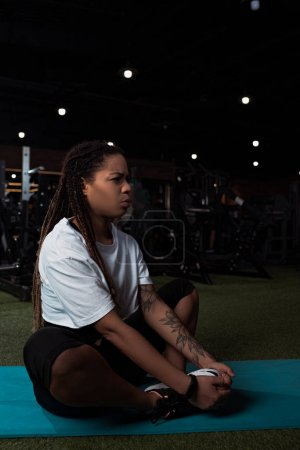 Worried and displeased african american woman sitting with crossed legs on fitness mat