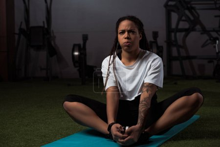 Photo for Tensed african american woman sitting with clenched hands on fitness mat - Royalty Free Image
