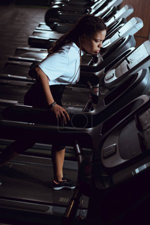 High angle view of african american woman running on treadmill in gym