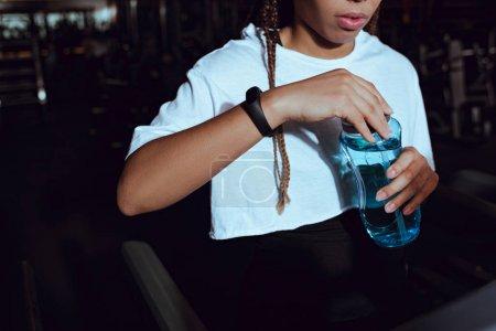 Photo pour Vue recadrée d'une femme afro-américaine tenant une bouteille d'eau sportive - image libre de droit
