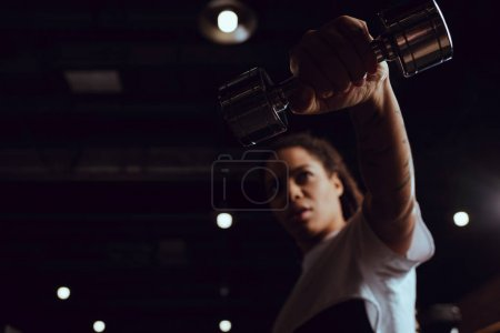 Photo pour Focus sélectif de la femme afro-américaine tenant haltère - image libre de droit