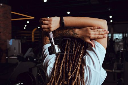 Back view of african american woman holding dumbbell