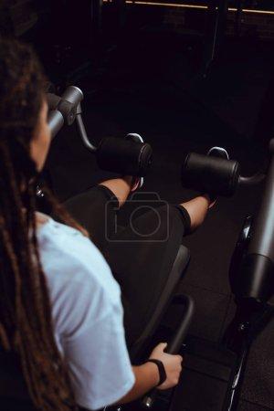 Photo pour Vue granuleuse d'une Africaine d'Amérique qui fait de l'exercice pour ses abdominaux au gymnase - image libre de droit