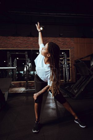 african american woman with dreadlocks stretching in gym