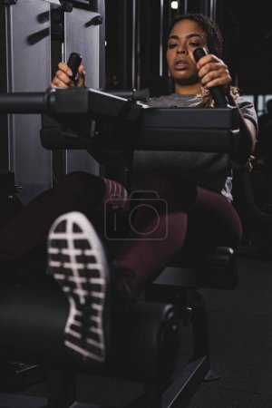 selective focus of african american girl working out on gym machine