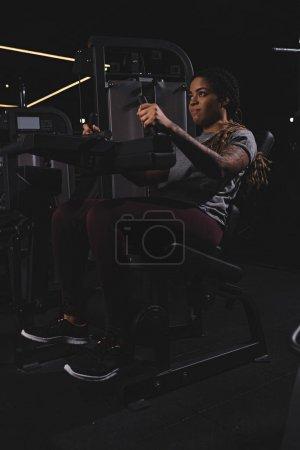 Photo pour Tatoué afro-américaine fille avec dreadlocks travailler sur machine de fitness - image libre de droit