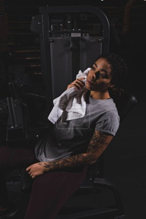 Photo pour Tatoué afro-américain fille tenant serviette près de la machine de fitness - image libre de droit