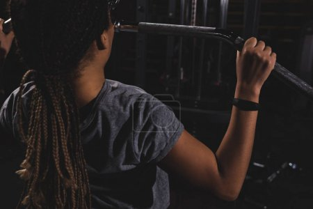 back view of young african american girl with smartwatch training in gym