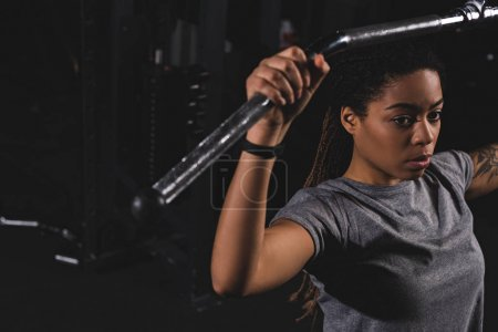 Photo for Selective focus of young african american girl with tattoo training on gym machine - Royalty Free Image