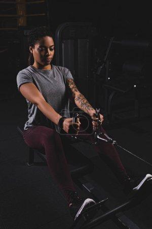 Photo pour Sportive africaine américaine sportive avec tatouage faisant de l'exercice dans la salle de gym - image libre de droit