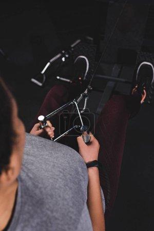 vista aérea de atlética afroamericana deportista con smartwatch ejercitando en gimnasio