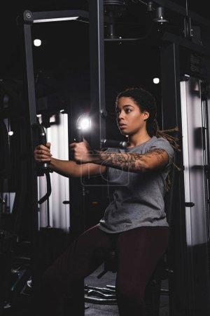 Photo pour Sportive afro-américaine fille avec tatouage formation sur machine de gymnastique - image libre de droit